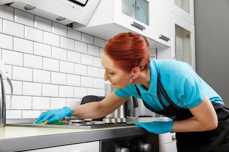 Женщина моет кухню